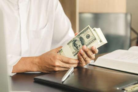 Photo pour Young business muslim man holding and showing money banknotes, finance concept. - image libre de droit