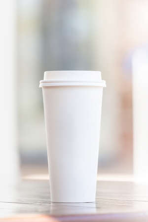 Photo pour Disposable coffee cup and smartphone on wooden table at cafe terrace blurred background - image libre de droit