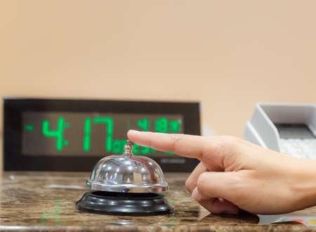 Photo pour Female hand ringing a service bell on hotel reception counter, travel concepts - image libre de droit