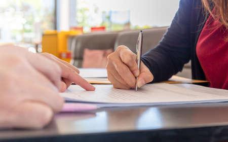 Foto de Close up of woman's hand with pen signing document, Deal concept - Imagen libre de derechos