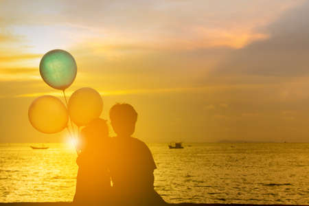 Foto de Silhouette of brother and sister sitting on the beach watching sunset with balloon in hand. - Imagen libre de derechos