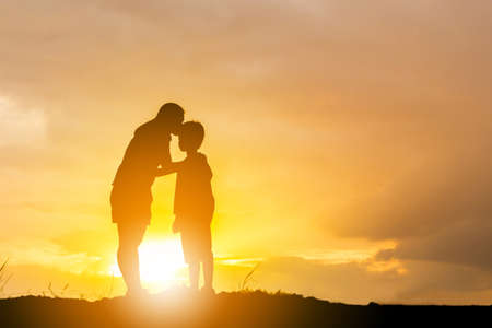 Photo pour Silhouette of a mother kissing his son in a forehead on the sunset summer day. - image libre de droit