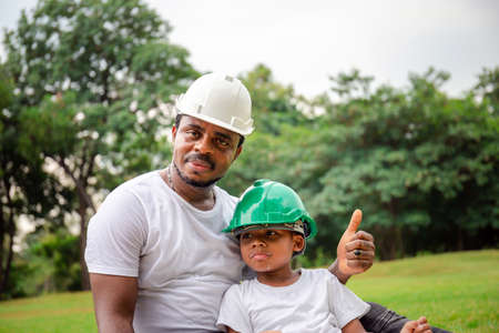 Photo pour Cheerful african american father and son in hard hat having a picnic in the park, Happiness family concepts - image libre de droit