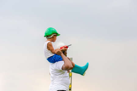 Photo pour Cheerful african american father and son in hard hat, Happy dad carrying son on shoulders - image libre de droit