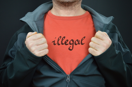 a man showing his t-shirt with the word illegal on it