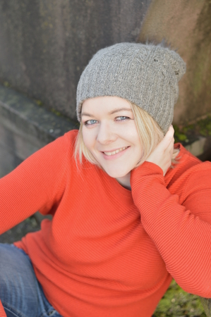 young pretty blond woman with orange sweater and gray kneeling outdoors sitting in a park leaning against a stone and smiling