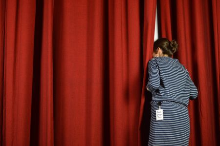 Photo pour Woman with a backstage looking over the red curtains on a stage - image libre de droit