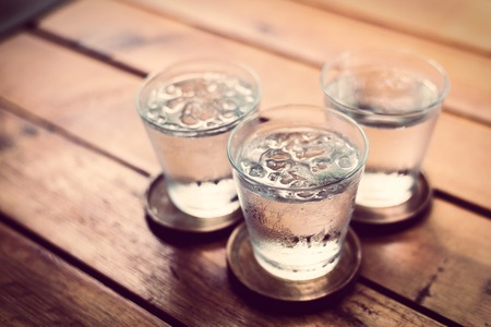 Drinking cold water into a  three glass placed on the wooden table.の写真素材