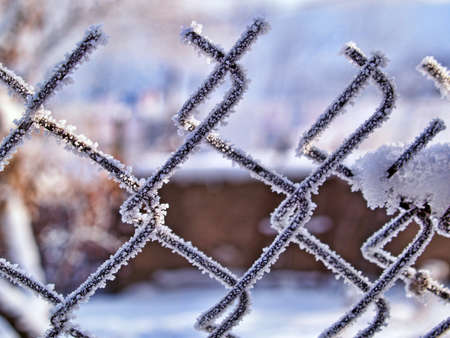 Frosted wire fence closeup with soft background.