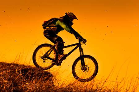 Photo pour Downhill mountain bike ride at sunset - image libre de droit
