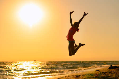 Foto de Happy girl jumping on the beach against the background of the sea and sunset. Sunset at sea. Girl jumping raising her hands up. - Imagen libre de derechos