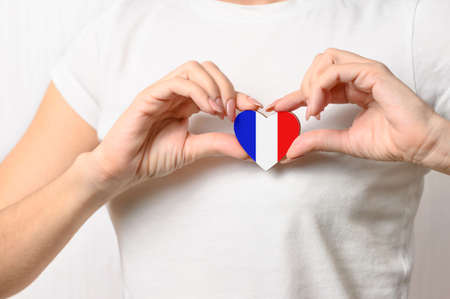 Photo pour Love France. A girl holds a heart in the form of a flag of France on her chest. French patriotism concept - image libre de droit