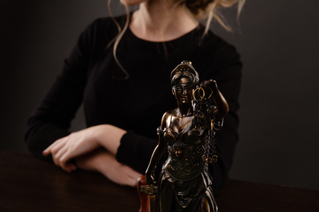 Closeup view of Statue of Justies and woman in a black clothes backgrownd