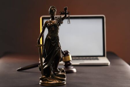 Statue of Justice and judge gavel. Laptop at behind