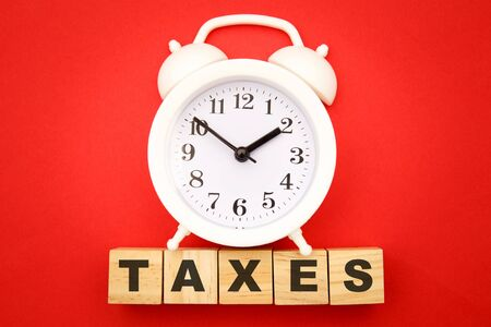 Photo pour Time to pay TAX concept. Wooden cubes and alarm clock on red background. - image libre de droit