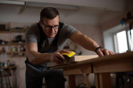 Photo pour Master carpenter skins wooden workpiece. - image libre de droit