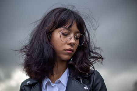 Photo pour Asian schoolgirl with glasses looking lost in thought about something. - image libre de droit