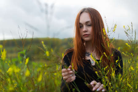 Photo pour A brooding red-haired girl with a sad face in a black jacket stands among the high wildflowers in the field. - image libre de droit