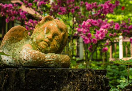 A weathered cherub garden ornament lies upon a wooden stump surrounded by green foliage and pink flowers