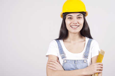 Photo pour Proud serious young woman architect or engineer with arms crossed as professional building supervisor concept isolated on white background - image libre de droit