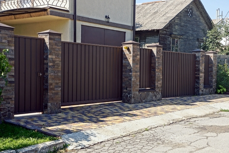 Photo for Gray brown iron fence in front of asphalt road - Royalty Free Image