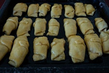 gray patties lie on a black frying pan before baking