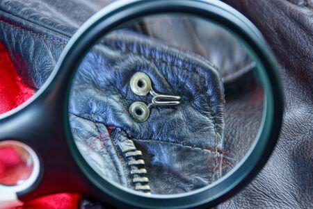 Photo pour black leather magnifier magnifies metal rivets and zip on brown leather clothes - image libre de droit