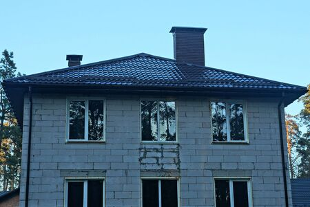 Photo for gray brick house with white windows under a brown tiled roof against the sky - Royalty Free Image