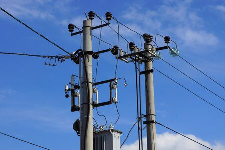 Photo pour two gray concrete pillars with electric wires on a background of blue sky and clouds on a sunny day - image libre de droit