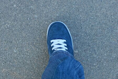 Photo pour leg in blue jeans and a suede sneaker with white lace stands on the gray asphalt on the street - image libre de droit