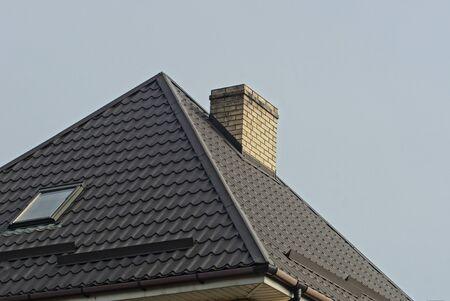 Foto de brick chimney on a tiled roof with a window on a background of gray sky - Imagen libre de derechos