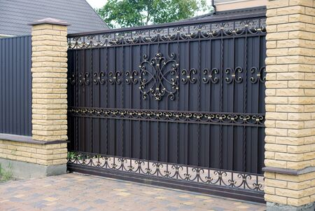 Photo pour large closed brown wrought-iron gate and brick fence on the sidewalk - image libre de droit