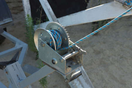 Photo pour part of a gray iron winch with a blue rope on the street - image libre de droit