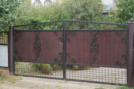 Photo pour one closed brown iron gate with a black wrought iron pattern on a rural street - image libre de droit