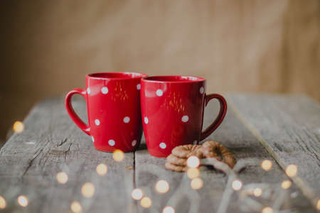 Photo pour Cozy atmosphere, chocolate cookies and maidens red cups, lights garlands in the foreground. Wooden rustic table. - image libre de droit