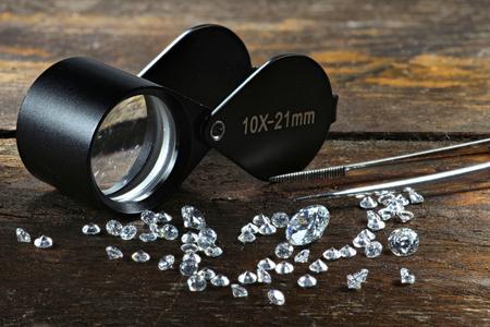 Photo pour cut diamonds with folding magnifier and tweezers on wooden background - image libre de droit