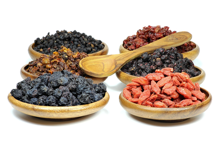 assortment of dried berries in wooden bowls isolated on white background