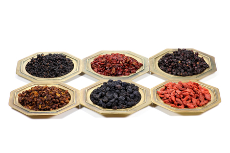 assortment of dried berries in brass bowls isolated on white background