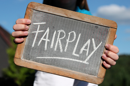 Photo for FAIRPLAY written with chalk on slate shown by young female - Royalty Free Image