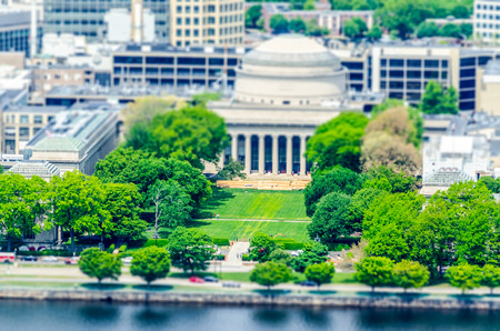 Boston Massachusetts Institute of Technology campus with trees and lawn aerial view with Charles River. Tilt-shift effect applied