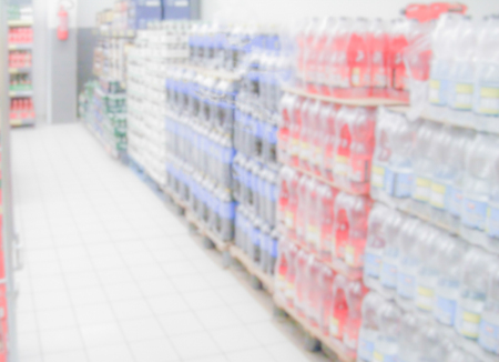 Defocused background within the aisles full of grocery goods in a supermarket or hypermarket convenience store. Intentionally blurred post production for bokeh effect