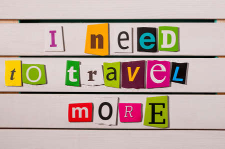 I need to travel more - written with color magazine letter clippings on wooden board. Concept  image.