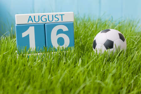 August 16th. Image of august 16 wooden color calendar on green grass lawn background with soccer ball. Summer day. Empty space for text.