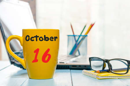 October 16th. Day 16 of month, morning tea in yellow cup with calendar on banker workplace background. Autumn time. Empty space for text.