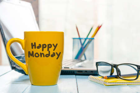 Photo pour Happy Monday motivational text on yellow morning coffee cup near computer at office workplace. Business background. - image libre de droit