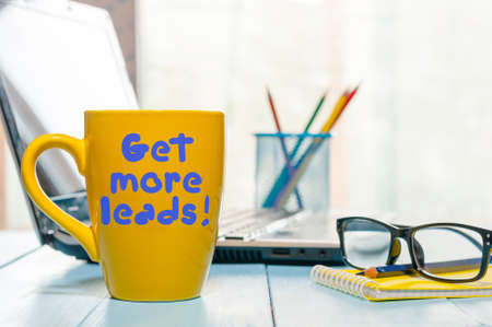 Foto de Get more leads motivation phrase on yellow cup of morning coffee or tea at business office workplace backgound. With empty space for text. - Imagen libre de derechos