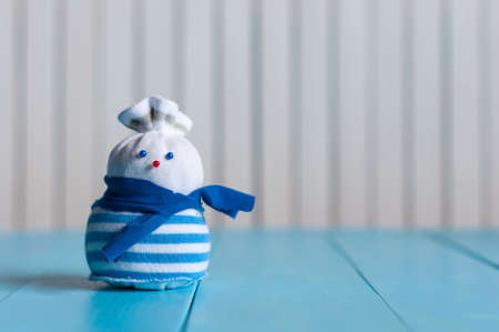 Funny little handmade snowman in a blue stripy sweater on wooden background. Christmas time, New year postcard with empty space.