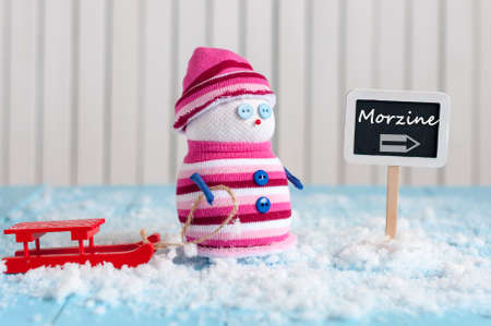 Signpost of the famous ski resort Morzine, France and Snowman with red sled stand near direction sign. Postcard.
