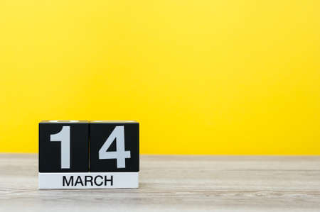 March 14th. Day 14 of month, calendar on table with yellow background. Spring time. Commonwealth and International pi days