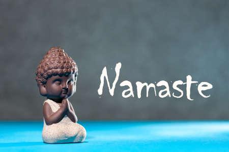 Foto de Close-up of little buddha meditating, focus on arms in Namaste gesture and text namaste - yoga and zen concept - Imagen libre de derechos